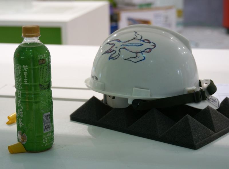 Каска и холодный зелёный чай ― незаменимые спутники любого рабочего. Кондиционеры ещё не включены, поэтому в павильоне душно